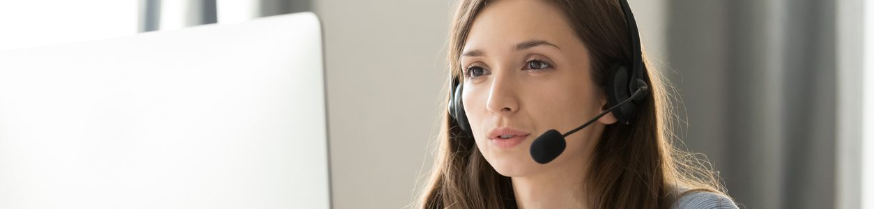 Serious young businesswoman in wireless headset call center agent telemarketer consulting client participating business video conference talk help as customer care service support helpline in office